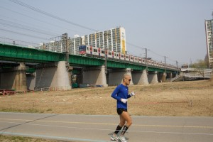 Man running along walking path by Han River, Line 4 subway heading towards Donjak Yuk (Station)